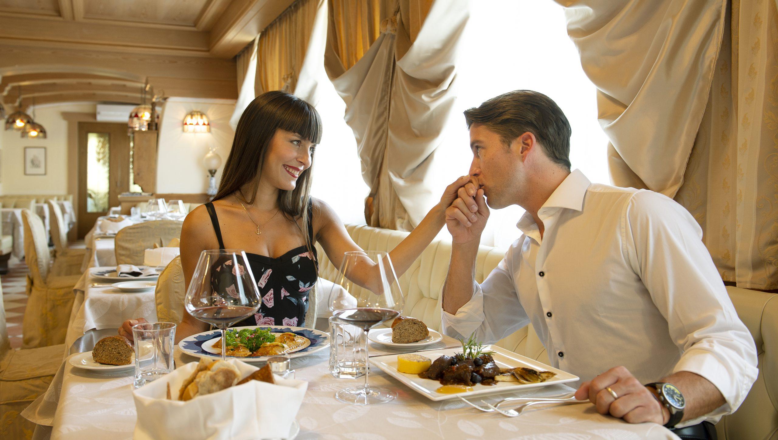 giovane coppia durante una cena tradizionale all'hotel alle alpi a moena