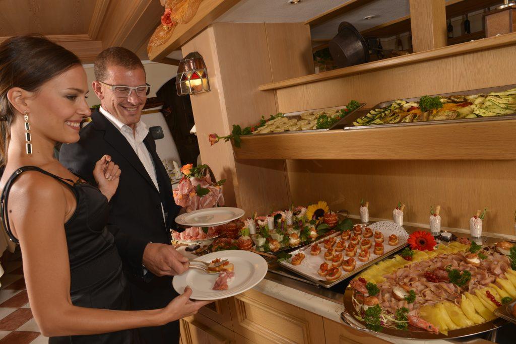 coppia al buffet gourmet proposto dall'hotel alle alpi a moena
