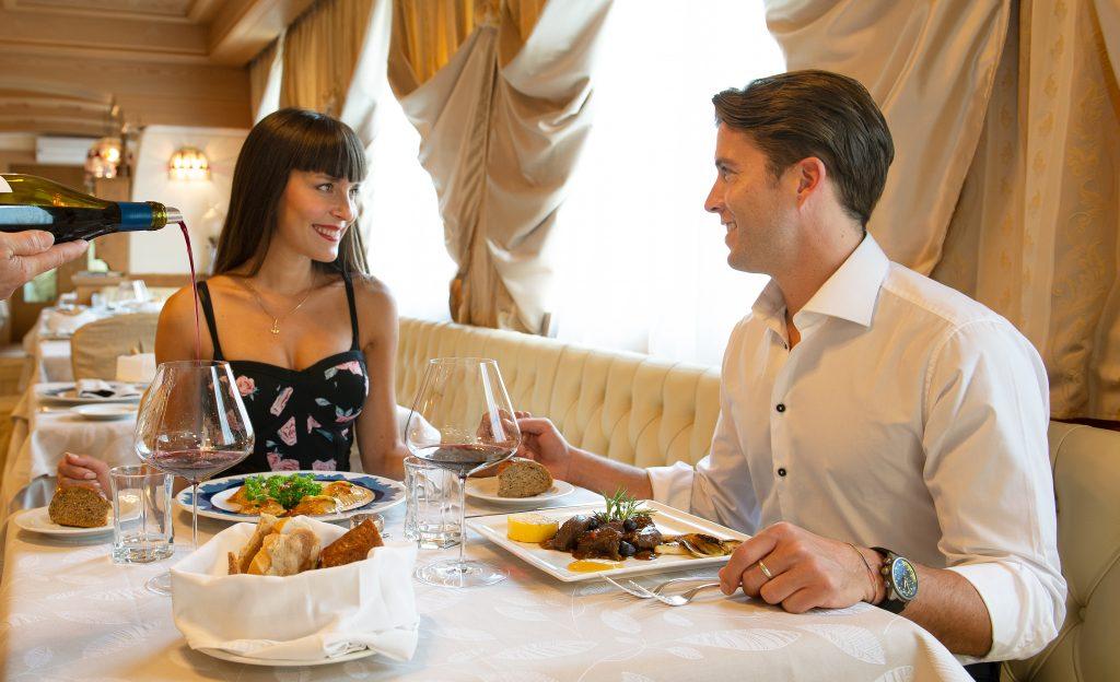 coppia consuma un ottimo pasto degustando vino presso il ristorante dell'hotel alle alpi