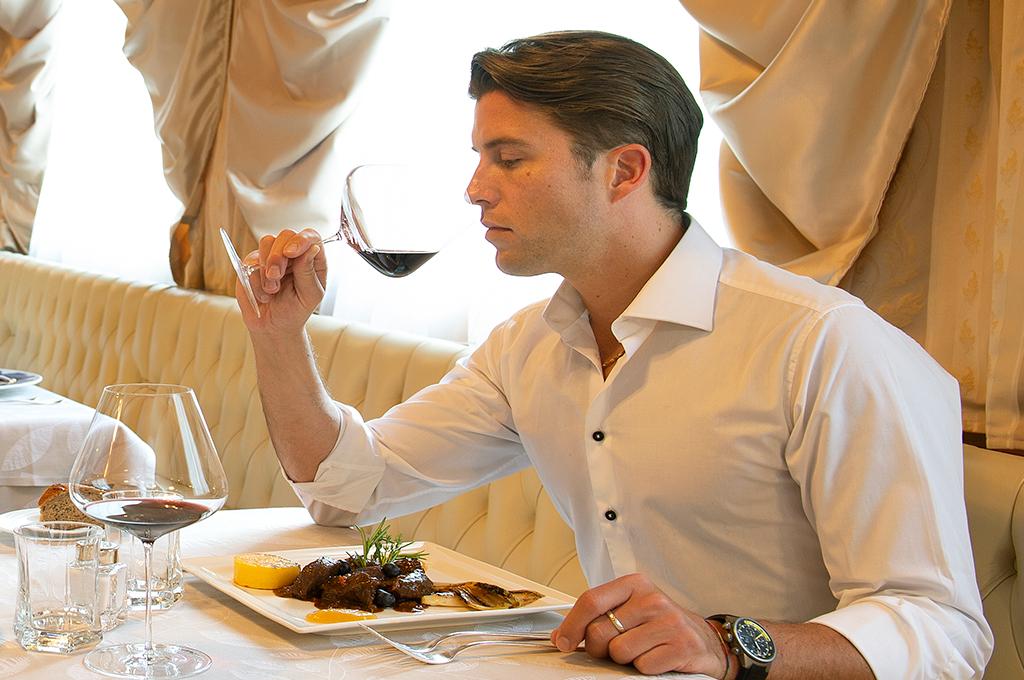 ragazzo degusta uno dei vini proposti dalla cantina dell'hotel alle alpi