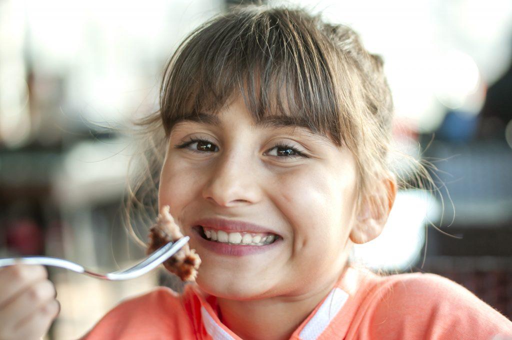 bambina sorridente mentre mangia