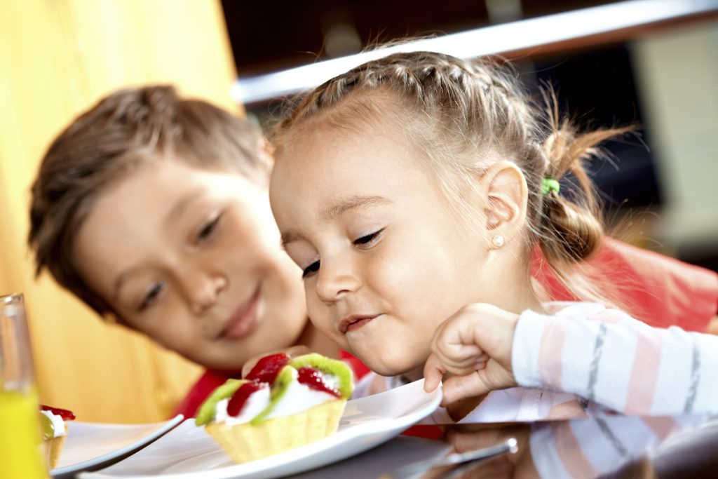 bambina mangia un pasticcino