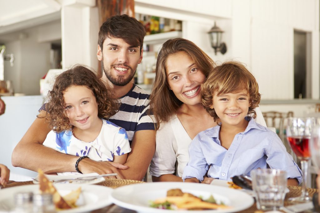 portrait of a family enjoying a meal in restaurant