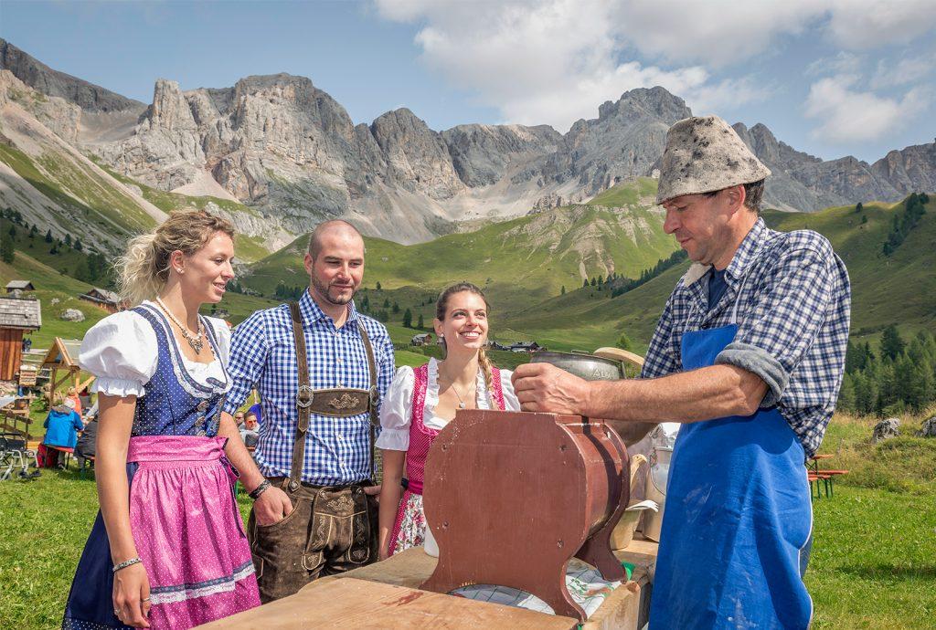 due donne e due uomini in malga con le dolomiti sullo sfondo