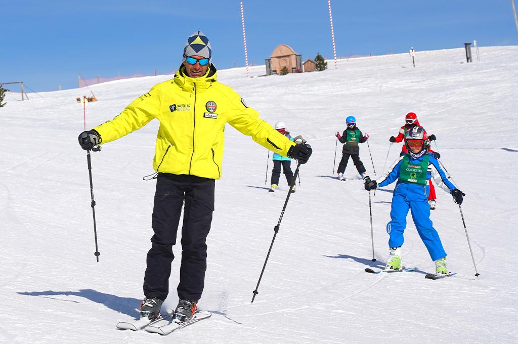 un maestro di sci della scuola di sci di moena a lezione con i bambini